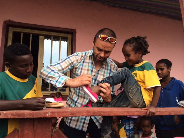 Uno de los miembros de la ong calzando a una niña